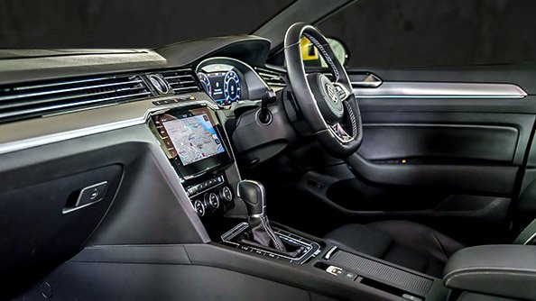 """Stunning design. The look-and-feel of the cockpit in Arteon's new R-Line trim is truly inspirational. The standard multifunction, leather sports steering wheel bears the """"R-Line"""" badge and boasts decorative stitching; it is complemented by """"Silver Rise"""" inlays in aluminium. The optional """"top-comfort"""" seats in """"Nappa"""" leather with """"carbon-style"""" inner faces of the side sections and decorative stitching and braiding, not to mention the """"R-Line"""" badge embroidered into the front seats make each ride a feast for the senses."""