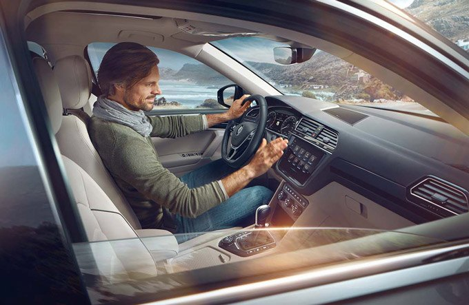 A guy using the gesture controlled infotainment system in a Tiguan Allspaec
