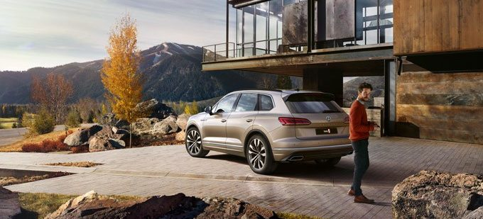 VW Touareg outside a luxury house and a guy