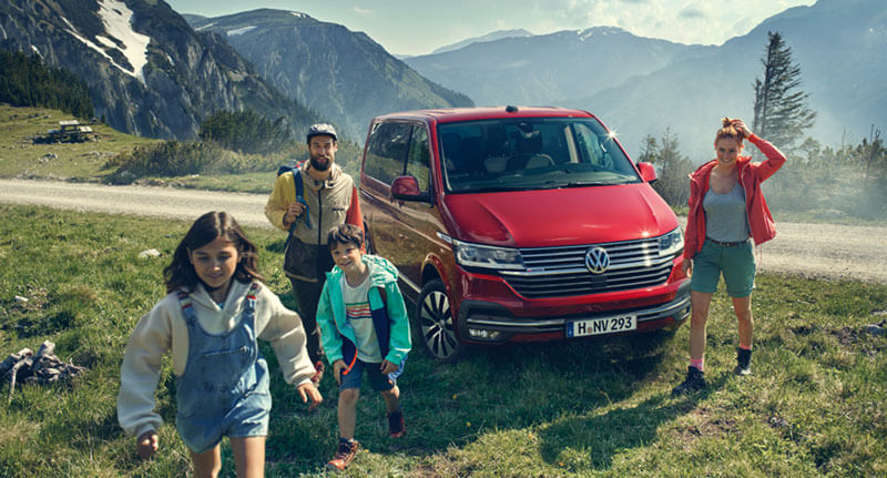 Family with their red VW multivan out for a walk in nature