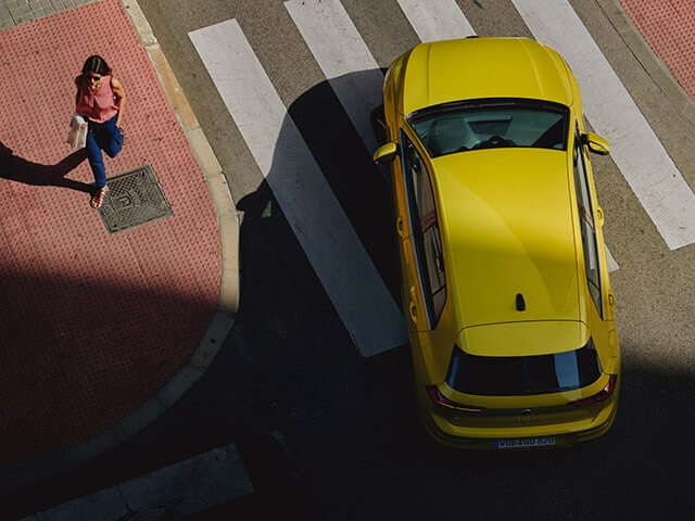 Birds eye view the a Yellow Golf MK8 at a crossing