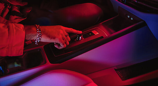 A woman using the instrument panel of a Golf M8, with ambient lighting